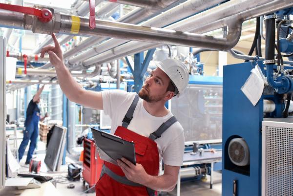 Arbeiter kontrolliert Industrieanlage